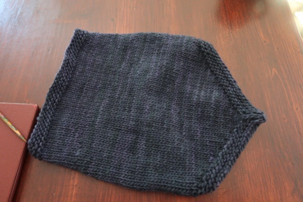 a dark blue hand-knitted cowl on a table